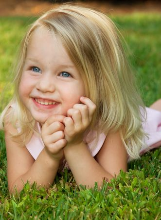 baby girls: Toddler girl smiling laying on grass, pretty girl Stock Photo