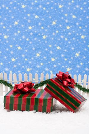 Christmas presents and white picket fence with green garland and red bow, merry Christmas photo