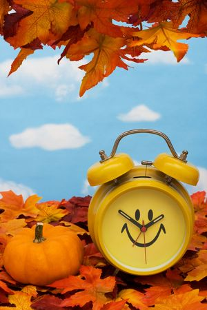Fall leaves with yellow clock and pumpkin on sky background, fall back time change photo
