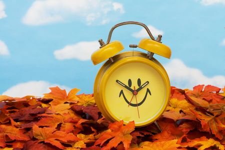 Fall leaves with yellow clock on sky background, fall back time change photo