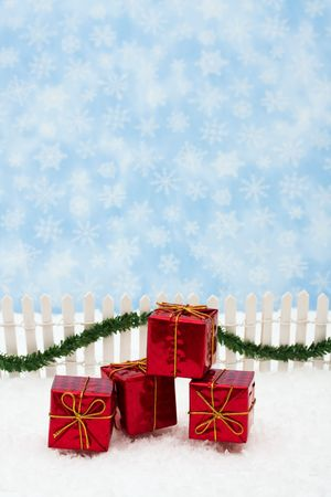 picket green: Christmas presents and white picket fence with green garland and red bow, merry Christmas