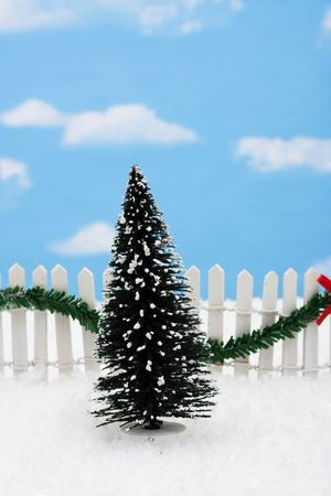 picket green: Evergreen tree and white picket fence with green garland and red bow, merry Christmas