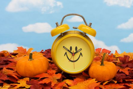 Fall leaves with yellow clock and pumpkins on sky background, fall back time change photo