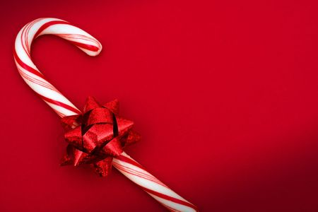 candy cane: Candy cane with red bow on red background, candy cane