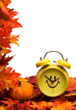 Fall leaves with yellow clock and pumpkin on white background, fall back time change