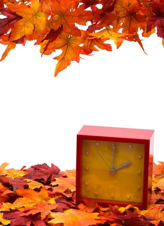 Fall leaves with red clock on white background, fall back time change Фото со стока