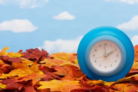 Fall leaves with blue clock on sky background, fall back time change photo