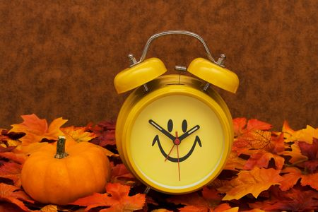 fall time: Fall leaves with yellow clock and pumpkin on brown background, fall back time change