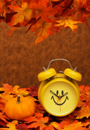 Fall leaves with yellow clock and pumpkin on brown background, fall back time change photo