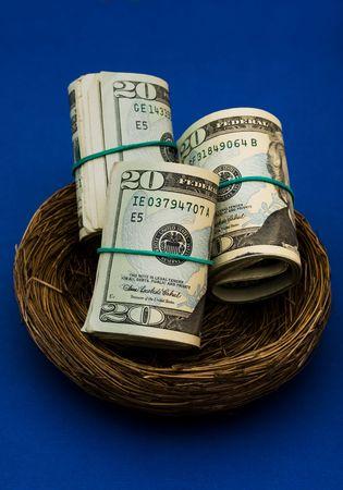 gniazdo jaj: Rolls dwudziestu Dolar rachunki posiedzenia w gniazdo na niebieskim tle, gniazdo jaj Zdjęcie Seryjne
