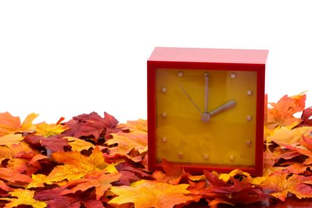 Fall leaves with red clock on white background, fall back time change photo