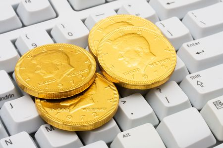 Computer keyboard with coins on it, making money online 免版税图像