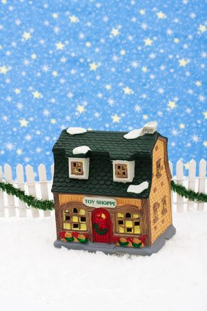 picket green: Toy store and white picket fence with green garland and red bow, merry Christmas Stock Photo