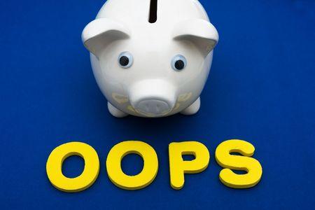Piggy bank met brieven spelling oops op zwarte achtergrond, uw spaargeld investeren