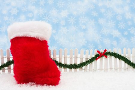 picket fence: Christmas stocking and white picket fence with green garland and red bow, merry Christmas