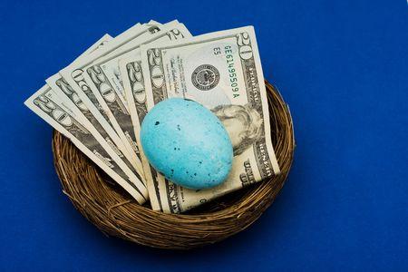 gniazdo jaj: Stack dwudziestu Dolar rachunki posiedzenia w gniazdo z jaj na niebieskim tle, gniazdo jaj Zdjęcie Seryjne