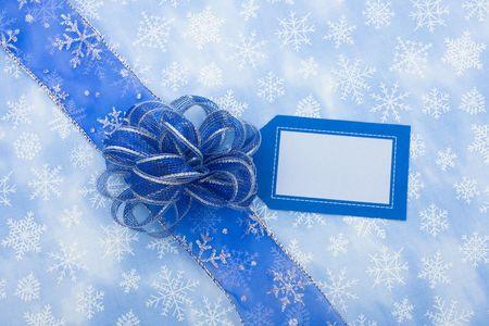 dar un regalo: List�n azul y blanco en la etiqueta de regalo copo de nieve de fondo con un arco haciendo presente