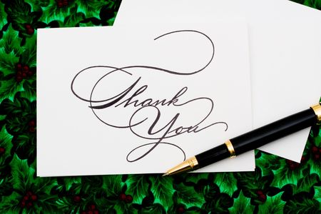 Thank you card and pen on leaf and holly berry background, thank you card