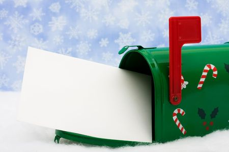 Green mailbox with blank card and the flag up sitting on snow with a snowflake background, mailbox photo