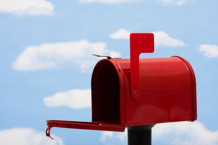red post box: Red mailbox filled with a blue sky and cloud background, mailbox Stock Photo