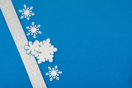 White ribbon with blank gift tag and snowflakes on blue background making a present photo