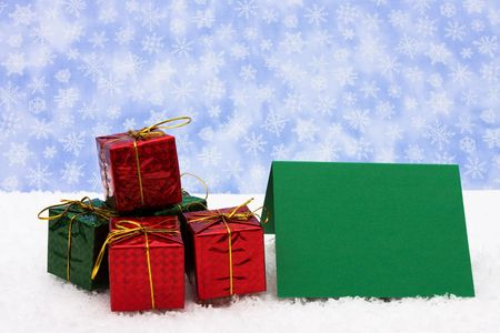 A stack of Christmas presents sitting on snow with a blank gift tag on a snowflake background, Christmas presents Stock Photo - 3857535