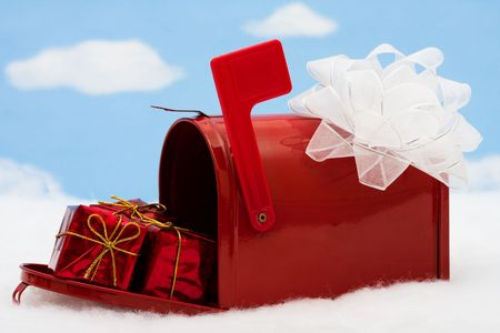 Red mailbox filled with presents and the flag up sitting on snow with a snowflake background, mailbox Stock Photo - 3857523
