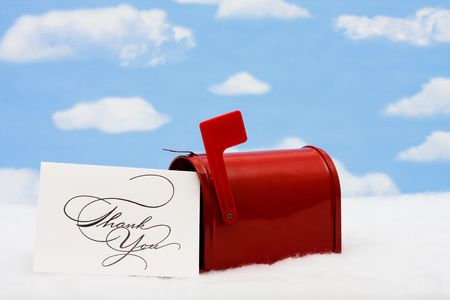 Red mailbox with white thank you card and the flag up sitting on snow with a snowflake background, mailbox