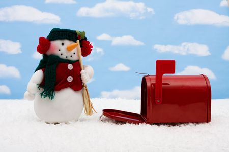 Red mailbox with the flag up sitting on snow with a snowman and a sky background, snowman and mailbox photo