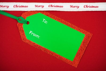 gist: Green and red blank gift tag with merry Christmas ribbon on red background, blank gift tag