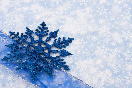 holidays: Blue snowflake and ribbon on snowflake background, holiday border Stock Photo