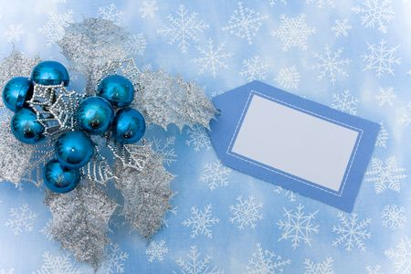 silver background: Silver leaves and blue berries with blank gift tag on snowflake background, Christmas decoration