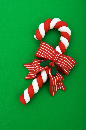 xmas background: Candy cane with red ribbon on green background, Christmas background Stock Photo