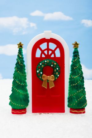 Red door with two green trees on sky background, Merry Christmas photo