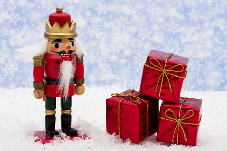 Nutcracker sitting on snow with three red presents on a snowflake background, nutcracker