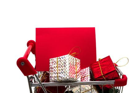 Shopping cart filled with presents and blank gift tag on white background, Christmas shopping photo
