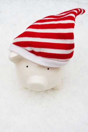 christmas savings: Piggy bank wearing a cap sitting on snow background, Christmas savings Stock Photo
