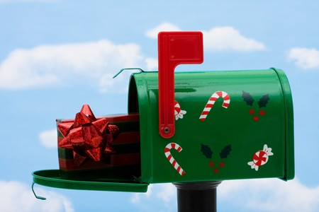 Green mailbox with a present inside and the flag up on a blue sky background, mailbox Stock Photo - 3964709