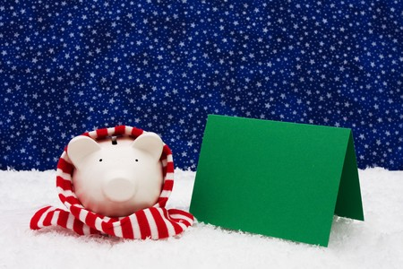 christmas savings: Piggy bank wearing a scarf on snow with blank card and a star background, Christmas savings Stock Photo