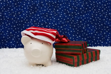 christmas savings: Piggy bank and Christmas presents sitting on snow with star background, Christmas savings