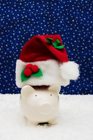 christmas savings: Piggy bank wearing Santa cap sitting on snow with star background, Christmas savings Stock Photo