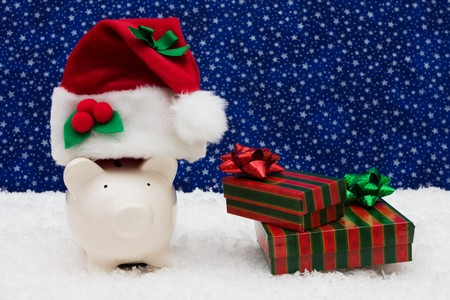 christmas savings: Piggy bank with presents sitting on snow with star background, Christmas savings