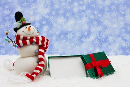 Gift box sitting with a snowman on snowflake background, gift box Stock Photo - 4052971