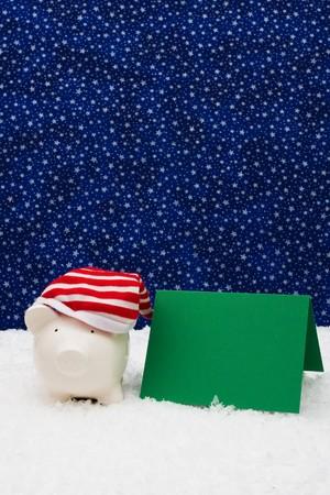 christmas savings: Piggy bank with blank card sitting on snow with star background, Christmas savings