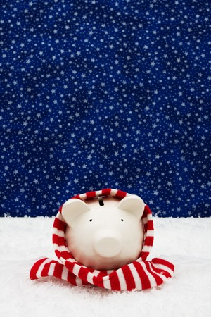 christmas savings: Piggy bank wearing a scarf on snow with star background, Christmas savings