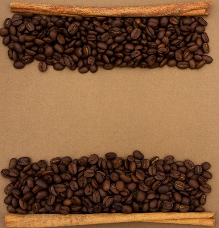 A mountain of coffee beans with a cinnamon stick sitting on a brown background, coffee bean border