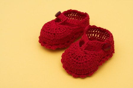 Red baby booties sitting on a yellow background, baby booties