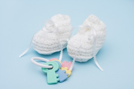Baby booties and rattle sitting on a blue background, baby booties