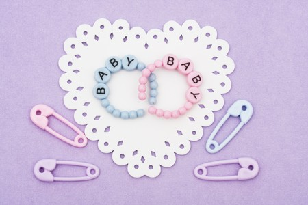 paper pin: Baby bracelets and safety pins sitting on a white heart on purple background, baby bracelets