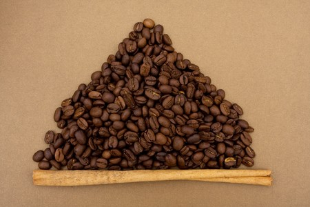 long bean: A mountain of coffee beans with a cinnamon stick sitting on a brown background, coffee bean border